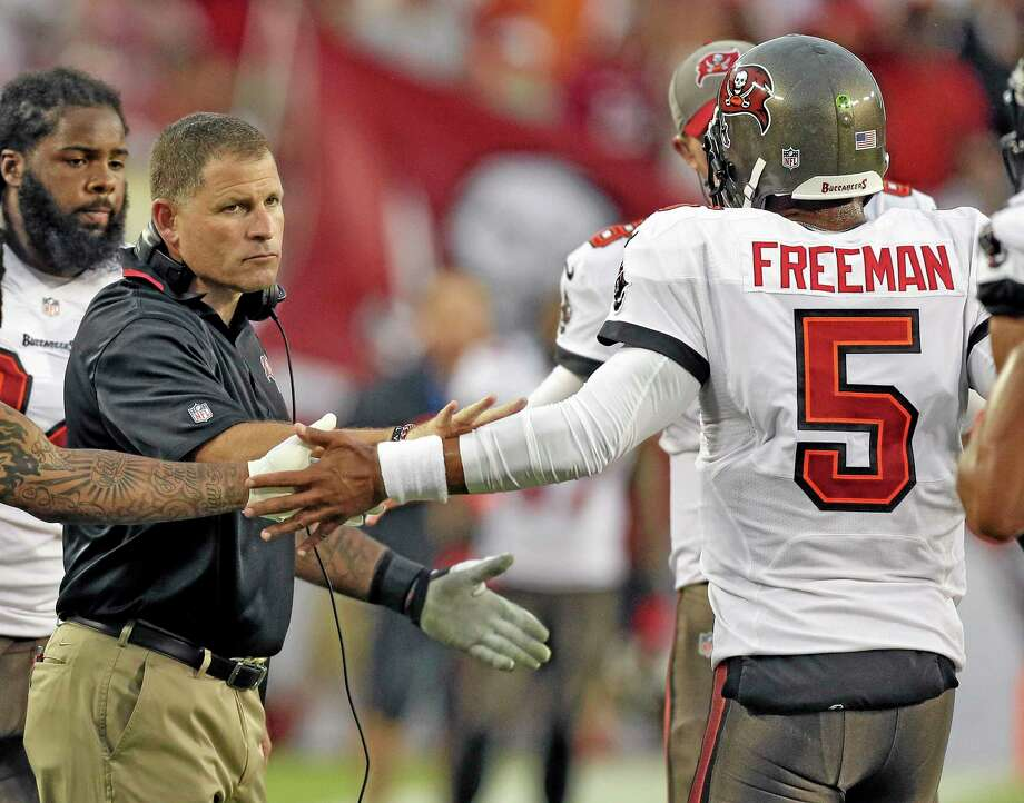 Buccaneers head coach Greg Schiano, left, shakes hands with quarterback Josh Freeman after Freeman threw a touchdown pass to wide receiver Kevin Ogletree during a Sept. 15 game against the New Orleans Saints in Tampa, Fla. The Buccaneers have benched Freeman and replaced him with rookie Mike Glennon. Wednesday's move came two days after Schiano insisted Freeman remained the starter because he gave the team the best chance to win. Photo: Chris O'Meara — The Associated Press  / AP