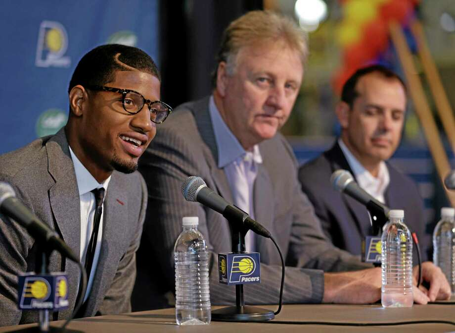 Pacers forward Paul George, left, talks about signing a multi-year contract extension with Indiana as team president Larry Bird, center, and head coach Frank Vogel look on Wednesday in Indianapolis. Photo: Michael Conroy — The Associated Press  / AP