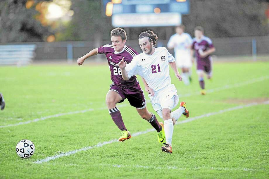 Shane Walker runs past Naugatuck's Osmund Kingstead, during Torrington's 3-2 loss to the Greyhounds. Photo: Laurie Gaboardi — Register Citizen