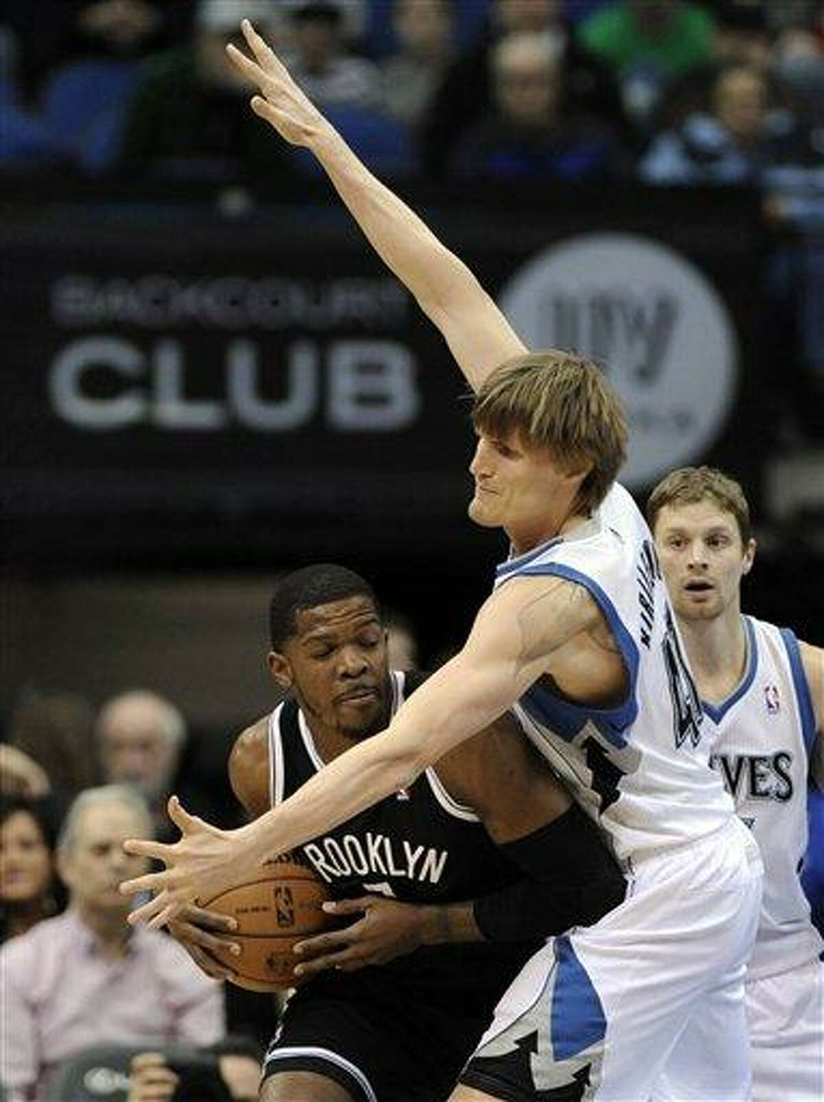 Brooklyn Nets' Joe Johnson, left, assumes a low profile as Minnesota Timberwolves' Andrei Kirilenko, of Russia, looms over him and Luke Ridnour, right, looks on in the first half of an NBA basketball game on Wednesday, Jan. 23, 2013, in Minneapolis. (AP Photo/Jim Mone)