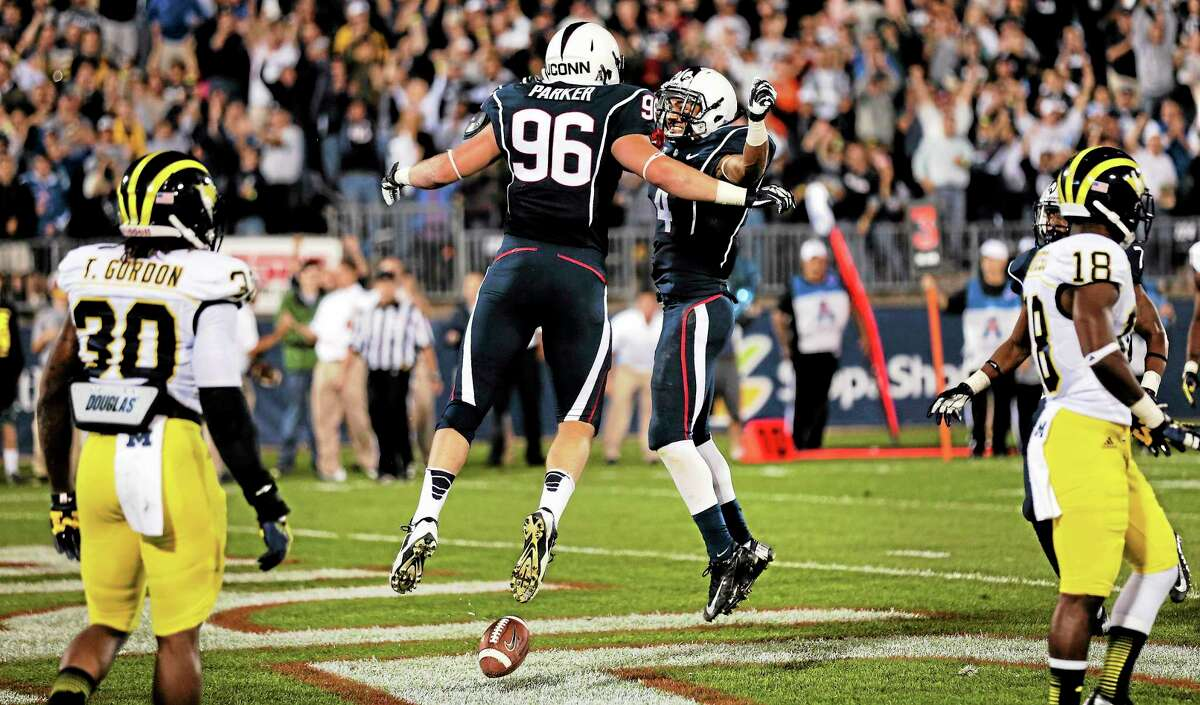 UConn tight end Spencer Parker (96) celebrates his touchdown with receiver Deshon Foxx during the second quarter of the Huskies' loss to Michigan on Saturday night at Rentschler Field in East Hartford.