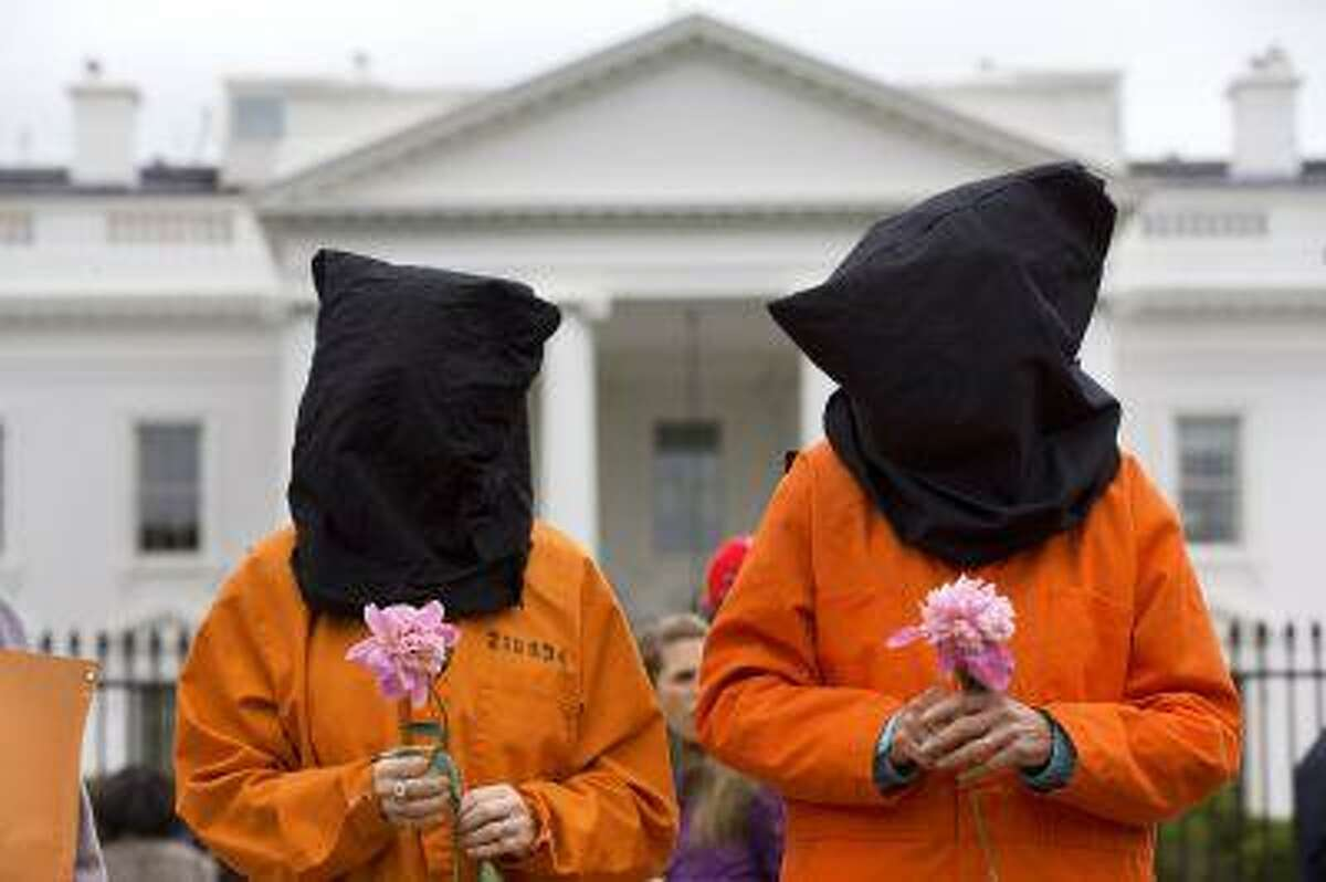 Holding a single flower each, two protesters wearing black hoods and orange jump suits take part in a demonstration in front of the White House in Washington, Friday, May 24, 2013, calling for the closing of the U.S. military prison at Guantanamo Bay, Cuba. The protest was organized by a coalition of groups including Witness Against Torture. (AP Photo/Jacquelyn Martin)