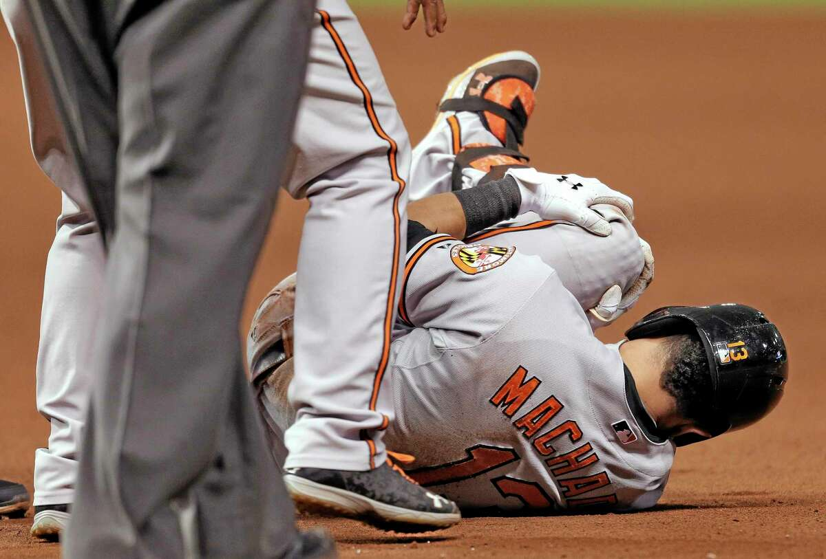 The Baltimore Orioles' Manny Machado grabs his left leg after it buckled while he was running to first base on a seventh-inning single off Tampa Bay Rays reliever Jake McGee on Monday in St. Petersburg, Fla.
