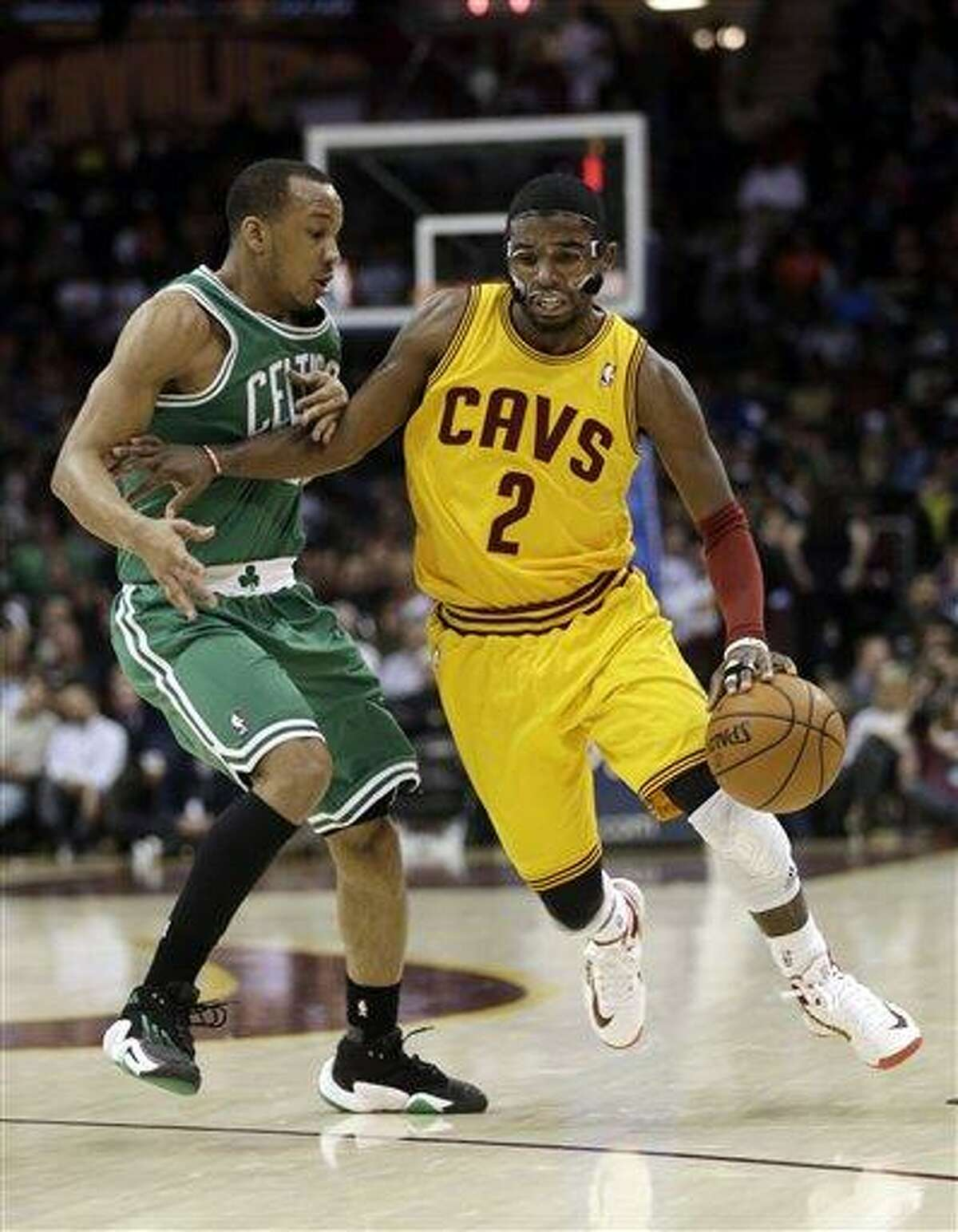 Cleveland Cavaliers' Kyrie Irving (2) drives past Boston Celtics' Avery Bradley (0) during the second quarter of an NBA basketball game Tuesday, Jan. 22, 2013, in Cleveland. (AP Photo/Tony Dejak)