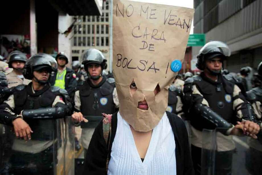 "A public university teacher wears a brown bag that reads in Spanish; ""Don't see me as a bag face,"" loosely translated as ""Don't take me for an idiot,"" during a protest in Caracas, Venezuela, Wednesday, May 22, 2013. Public university teachers demanding wage increases marched today accompanied by students. (AP Photo/Fernando Llano) Photo: ASSOCIATED PRESS / AP2013"