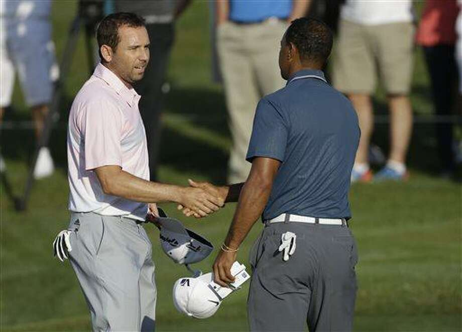 "In this photo made May 12, 2013, Sergio Garcia, of Spain, left, shakes hands with Tiger Woods at the end of the third round of The Players championship golf tournament at TPC Sawgrass in Ponte Vedra Beach, Fla. Garcia apologized to Woods on Wednesday, May 22, 3013, for saying he would have ""fried chicken"" at dinner with his rival, a comment that Woods described as hurtful and inappropriate. (AP Photo/Gerald Herbert) Photo: AP / AP"