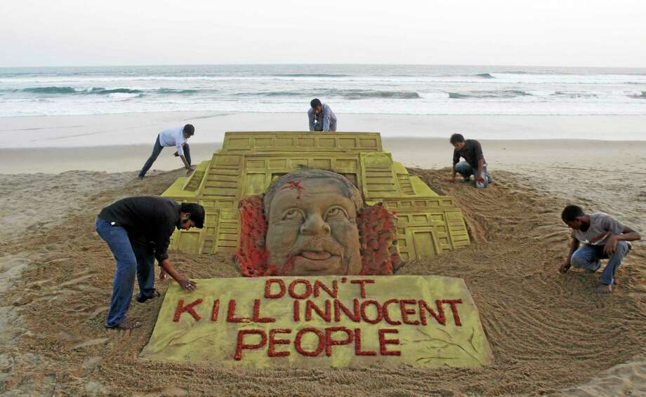Indian sand artist Sudarshan Pattnaik, foreground left and his team pay tributes to the victims of the terror attack on a Kenya mall by creating a sand sculpture on the Bay of Bengal coast in Puri, Orissa state, India, Tuesday, Sept. 24, 2013. (AP Photo/Biswaranjan Rout) Photo: AP / AP