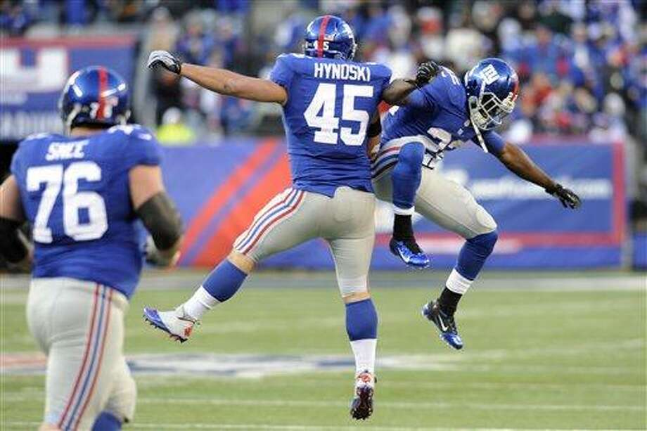 New York Giants fullback Henry Hynoski (45) celebrates a touchdown catch with teammate David Wilson, right, as Chris Snee (76) looks on during the second half of an NFL football game Sunday, Dec. 30, 2012 in East Rutherford, N.J. (AP Photo/Bill Kostroun) Photo: AP / FR51951 AP