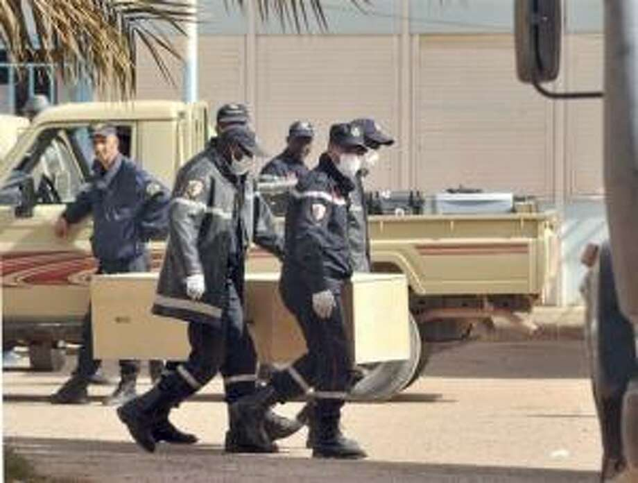 Algerian firemen carry a coffin containing a person killed during the gas facility hostage situation at the morgue in Ain Amenas, Algeria, Monday, Jan. 21, 2013. At least 81 people have been reported dead, including 32 Islamist militants, after a bloody, four-day hostage situation at Algeria's remote Ain Amenas natural gas plant. AP Photo/Anis Belghoul Photo: AP / AP