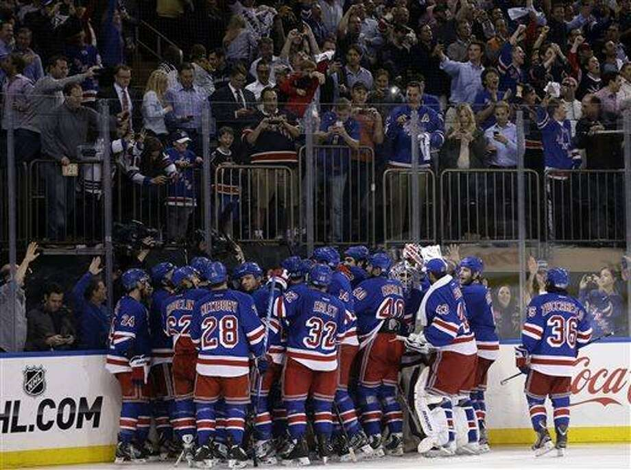 The New York Rangers gather around Chris Kreider after he scored the winning goal during the overtime period in Game 4 of the Eastern Conference semifinals against the Boston Bruins in the NHL hockey Stanley Cup playoffs in New York, Thursday, May 23, 2013, in New York. The Rangers defeated the Bruins 4-3. (AP Photo/Seth Wenig) Photo: AP / AP