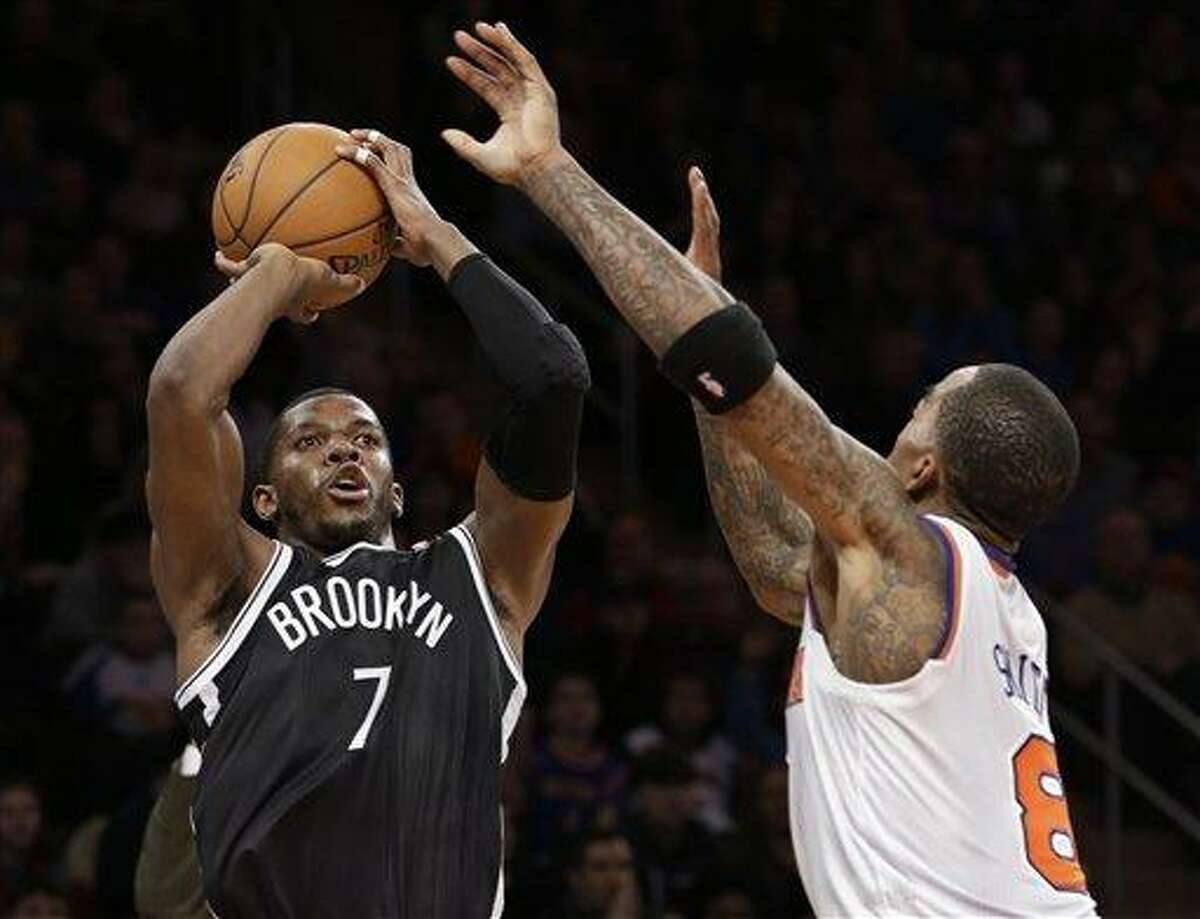Brooklyn Nets guard Joe Johnson (7) shoots a 3-pointer over New York Knicks guard J.R. Smith (8) in the second half of their NBA basketball game at Madison Square Garden in New York, Monday, Jan. 21, 2013. The Nets won 88-85. (AP Photo/Kathy Willens)