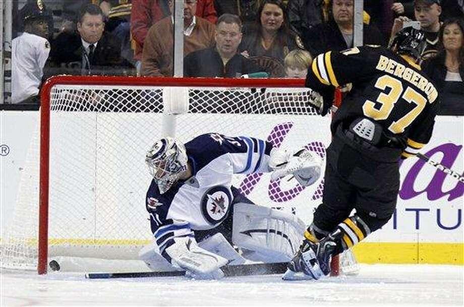 Boston Bruins' Patrice Bergeron (37) scores on Winnipeg Jets' Ondrej Pavelec during the shootout in an NHL hockey game in Boston, Monday, Jan. 21, 2013. The Bruins won 2-1. (AP Photo/Michael Dwyer) Photo: ASSOCIATED PRESS / AP2013