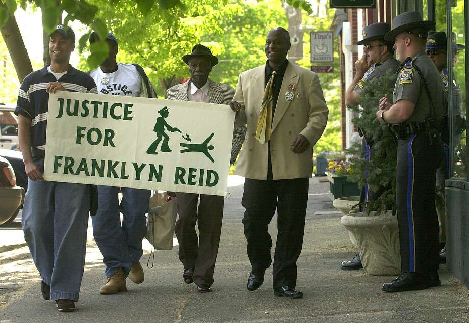 Supporters of the family of Franklyn Reid carry a sign down the street in Litchfield, Conn., Tuesday, May 20, 2003, outside Superior Court. Former New Milford Police Officer Scott Smith was due in court to enter a plea in connection with the 1998 shooting death of Reid, a black suspect who was wanted by police for failing to appear in court and for probation violations. Smith rejected a plea deal that would have spared him prison in the fatal shooting of Reid, the victim's family and their lawyer said.(AP Photo/Bob Child) Photo: AP / AP