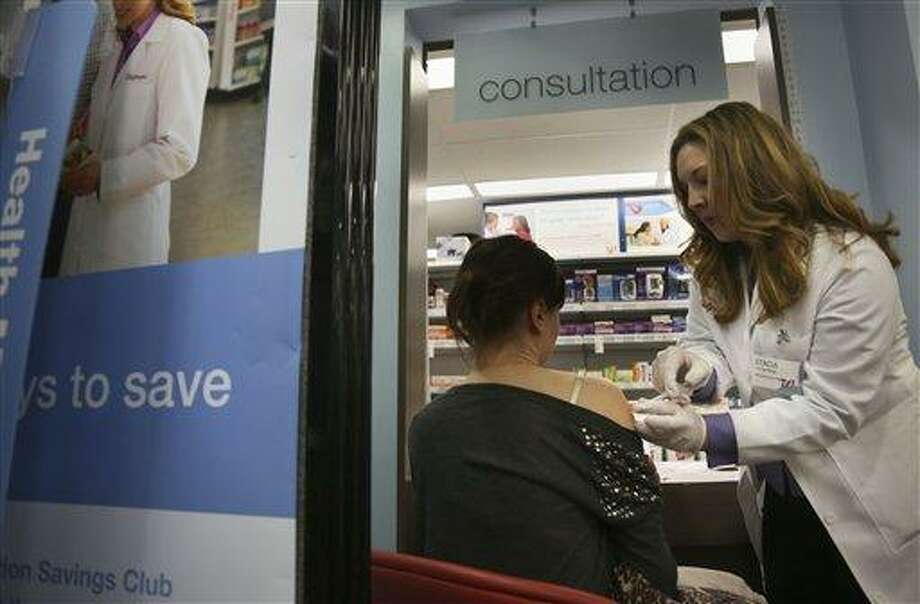 Pharmacist Stacia Woodcock, a pharmacy manager for Walgreens in New York, administers a flu vaccine on site on Monday, Jan. 14, 2013. Some New York City pharmacies and clinics reported flu vaccine shortages caused by widespread outbreaks, but the city's Health Department said shortages are in individual locations and don't reflect a larger supply problem. (AP Photo/Bebeto Matthews) Photo: AP / AP