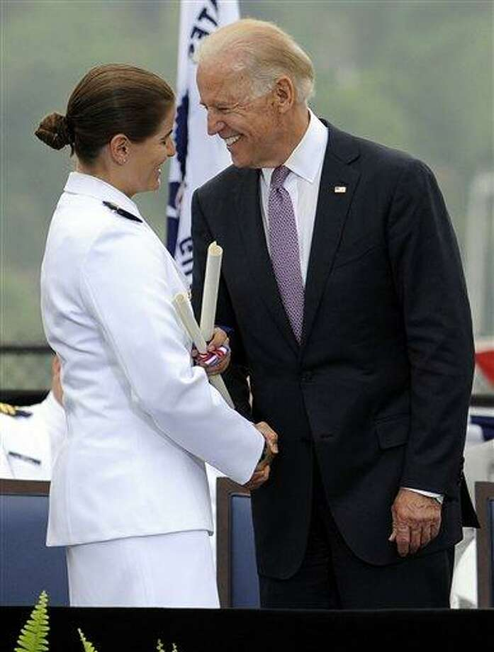 Newly commissioned officer Holli Bastinck shakes hands with Vice President Joe Biden during commencement for the U.S. Coast Guard Academy in New London, Conn., Wednesday, May 22, 2013. The vice president told graduating cadet that the nation will increasingly rely on the service for missions including more remote Arctic operations, port security and support of other U.S. military branches in securing maritime shipping around the world.   (AP Photo/Jessica Hill) Photo: AP / FR125654 AP