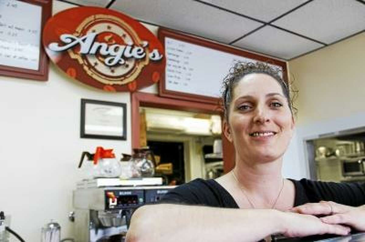 """Co-owner Angie Rimbach poses on top of a pastry and bagel rack inside Angie's Coffee & More on Wednesday, May 22. The shop is new, and is located on 336 North Elm Street in Torrington. It will have it's grand opening on Thursday, and will feature a pair of camels with signs that read """"Get over the hump, grab a cup of coffee."""" The shop is one of four new businesses that have sprung up in Torrington since February. (ESTEBAN L. HERNANDEZ/REGISTER CITIZEN)"""
