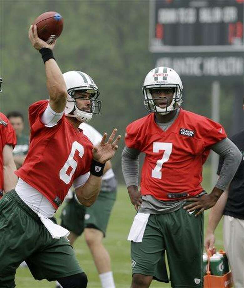 New York Jets' Mark Sanchez (6) throws a pass as Geno Smith (7) looks on as the quarterbacks practice during NFL football practice in Florham Park, N.J., Wednesday, May 22, 2013. (AP Photo/Mel Evans) Photo: AP / AP