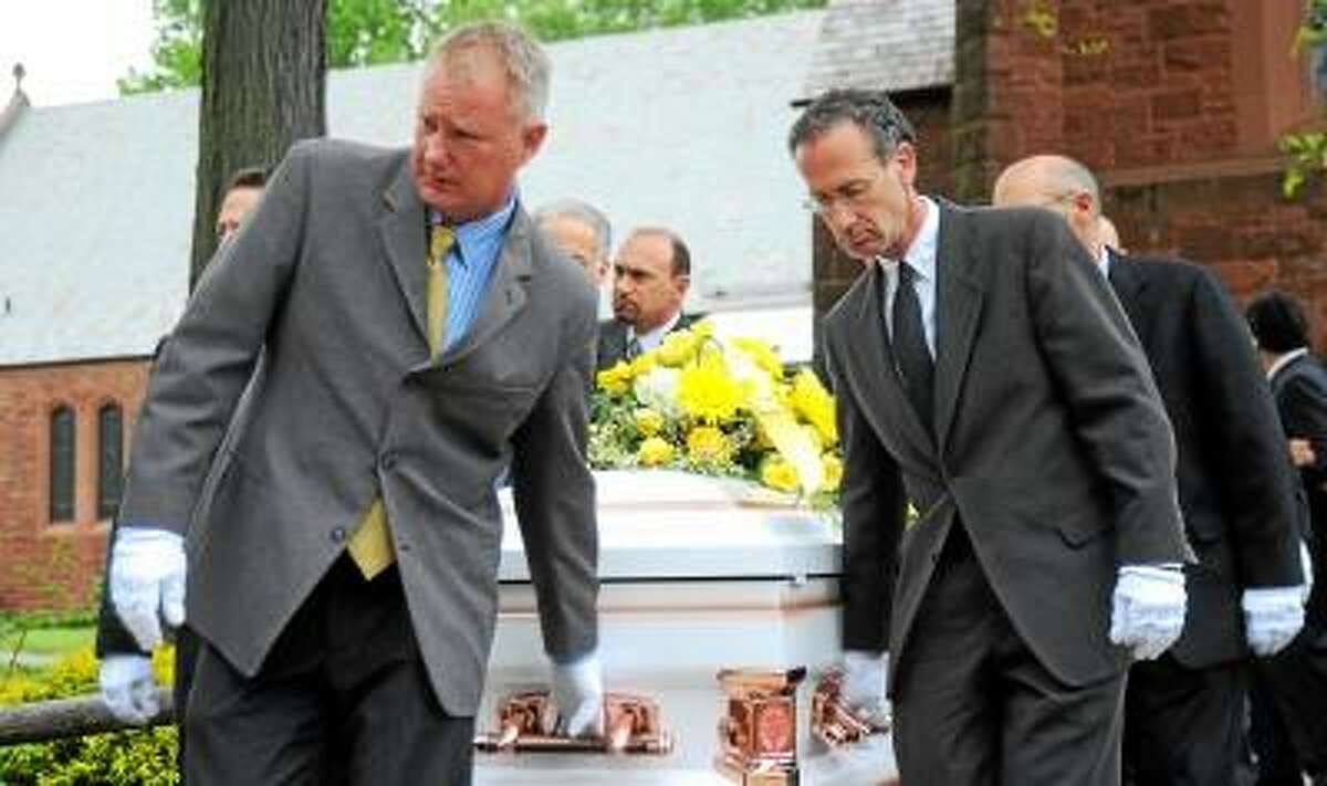 New Haven Register's photojournalists Peter Casolino (left) and Arnold Gold (right) carries the casket out of the Church of the Blessed Sacrement, Hamden, after the funeral service. Darren Yip/Register