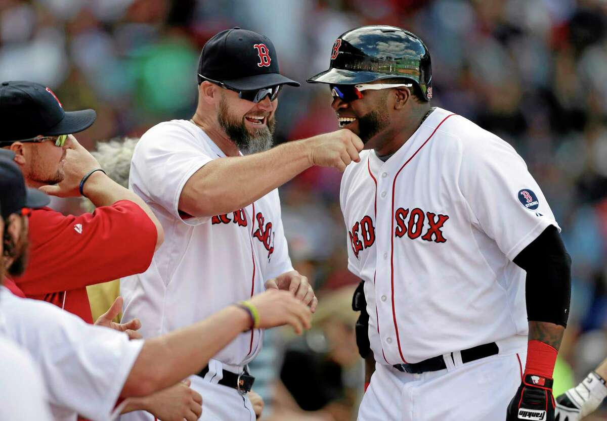 David Ortiz, right, is welcomed to the dugout by Red Sox's David Ross, center left, after Ortiz hit a home run off R.A. Dickey in the sixth inning Sunday.