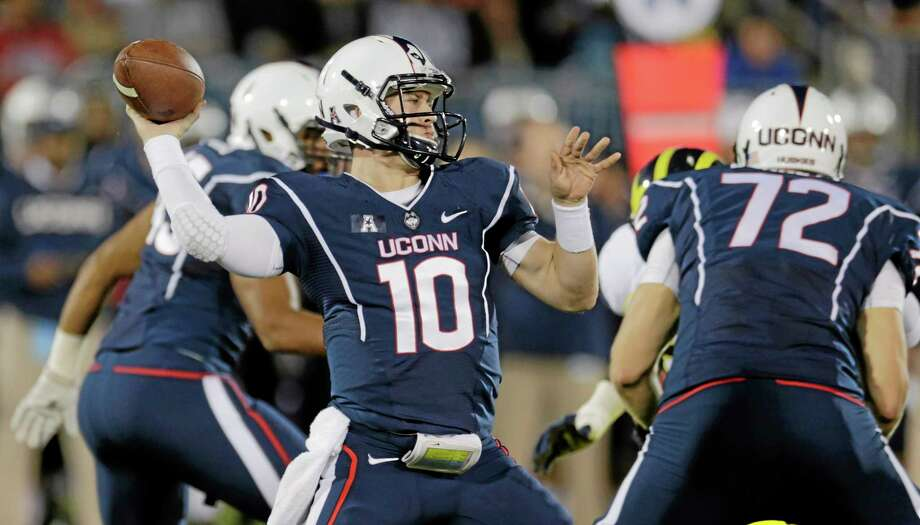 UConn quarterback Chandler Whitmer throws against Michigan during the first quarter Saturday night. Photo: Charles Krupa — The Associated Press  / AP
