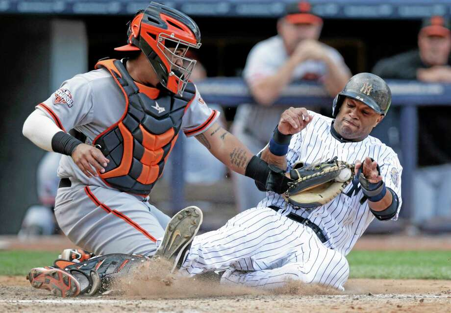 Giants catcher Hector Sanchez tags out the Yankees' Robinson Cano at the plate after Eduardo Nunez hit into an eighth-inning fielder's choice for the third out Sunday. Photo: Kathy Willens — The Associated Press  / AP