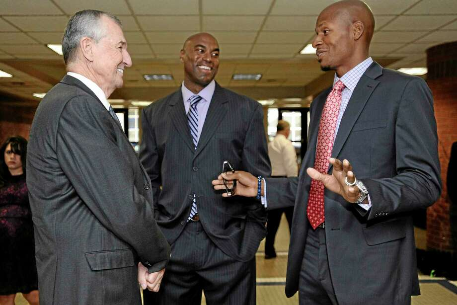 Former UConn basketball coach Jim Calhoun, left, speaks with former players Scott Burrell, center, and Ray Allen before a program honoring his coaching career Sunday in Storrs. Photo: Jessica Hill — The Associated Press  / FR125654 AP