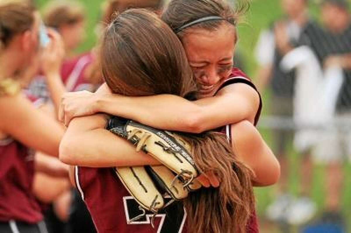 Photo by Marianne Killackey/Special to Register Citizen Aunchlee Reilly embraces teammate Brittany Young after the Lady Raiders clinch the NVL Softball title.