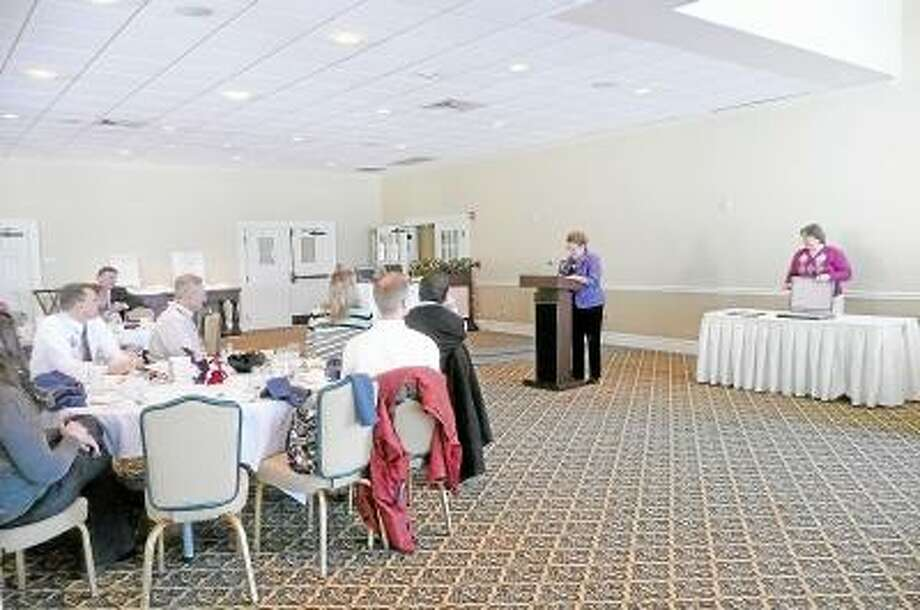 KATE HARTMAN/Register Citizen Chamber president JoAnn Ryan, at the podium, speaks about Sandy Roberts, this year's recipient of a lifetime achievement award, during the United Way of Northwest Connecticut's annual meeting and luncheon at the Torrington Country Club in Goshen.