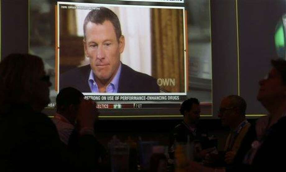 A video screen at a hotel restaurant in Grapevine, Texas, Friday, Jan. 18, 2013, shows a replay telecast of a segment of Lance Armstrong being interviewed by Oprah Winfrey,  Reversing more than a decade of denials,  Armstrong confessed to using performance-enhancing drugs to win the Tour de France cycling during the interview that aired night before. The second part of the interview will air tonight. (AP Photo/LM Otero) Photo: AP / AP