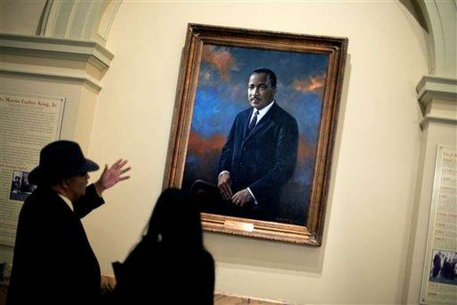 Rep. Roger Bruce, D-Atlanta, left, points out the hanging portrait of Rev. Martin Luther King Jr., to his assistant, Sophia Andrade, following a service celebrating King's birthday inside the Georgia State Capitol, Thursday, Jan. 17, 2013, in Atlanta. (AP Photo/David Goldman) Photo: AP / AP