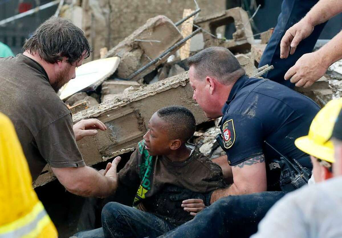 A boy is pulled from beneath a collapsed wall at the Plaza Towers Elementary School following a tornado in Moore, Okla., Monday, May 20, 2013. A tornado as much as a mile (1.6 kilometers) wide with winds up to 200 mph (320 kph) roared through the Oklahoma City suburbs Monday, flattening entire neighborhoods, setting buildings on fire and landing a direct blow on an elementary school. (AP Photo/ Sue Ogrocki)