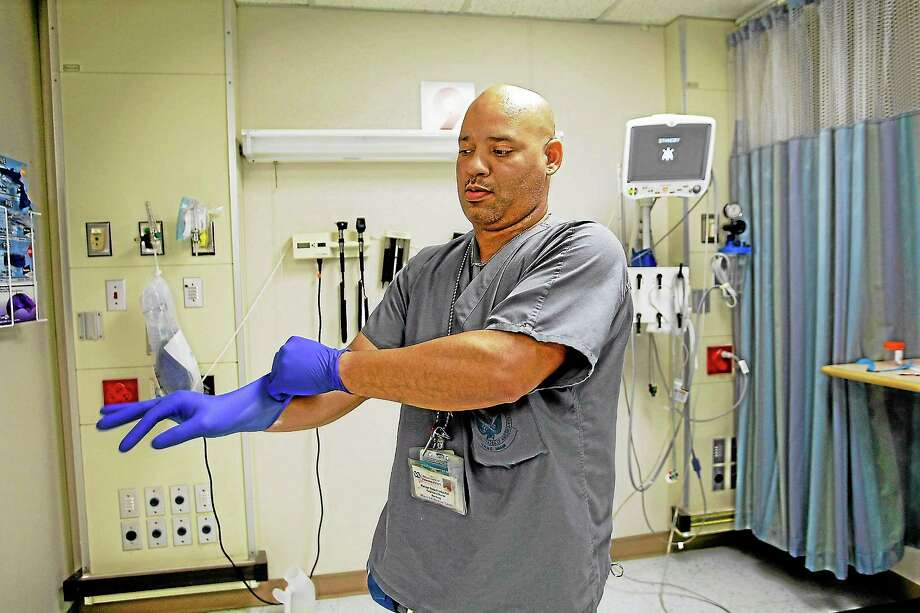 Miami VA Medical Center hospital registered nurse, Rafael Sepulveda, pulls on rubber gloves while attending to patients in the Emergency room in Miami, Fla. Photo: Joe Raedle — Getty Images File Photo  / 2007 Getty Images