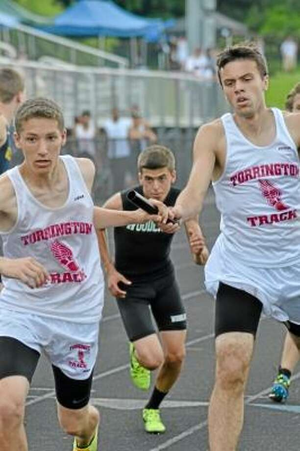 Pete Paguaga/Register Citizen  Matthew Titus passes the baton to John Pirla during their third place finish in the 4X800 meter relay.