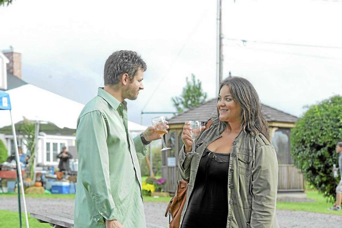 Justin Sherman and Lindsey Butler enjoy wine at the Sunset Meadow Vineyard harvest festival on Saturday in Goshen.