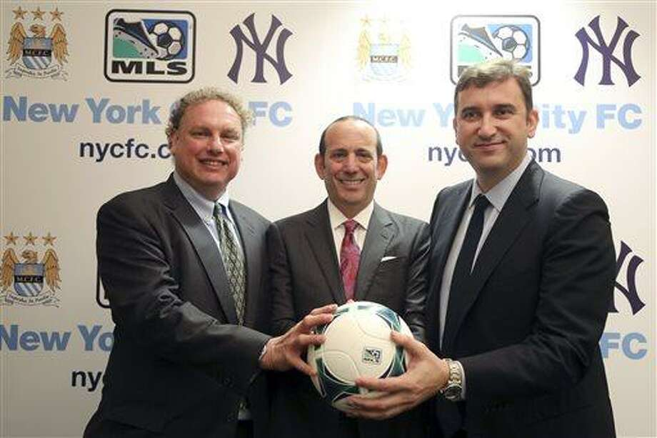 New York Yankees president Randy Levine, left, Major League Soccer Commissioner Don Garber, center, and Manchester City CEO Ferran Soriano pose for a photo at the MLS headquarter in New York, Tuesday, May 21, 2013.  The New York Yankees are partnering with Manchester City to own Major League Soccer's 20th team, which will be called New York City Football Club and plans to start play in the 2015 season. (AP Photo/Mary Altaffer) Photo: AP / AP