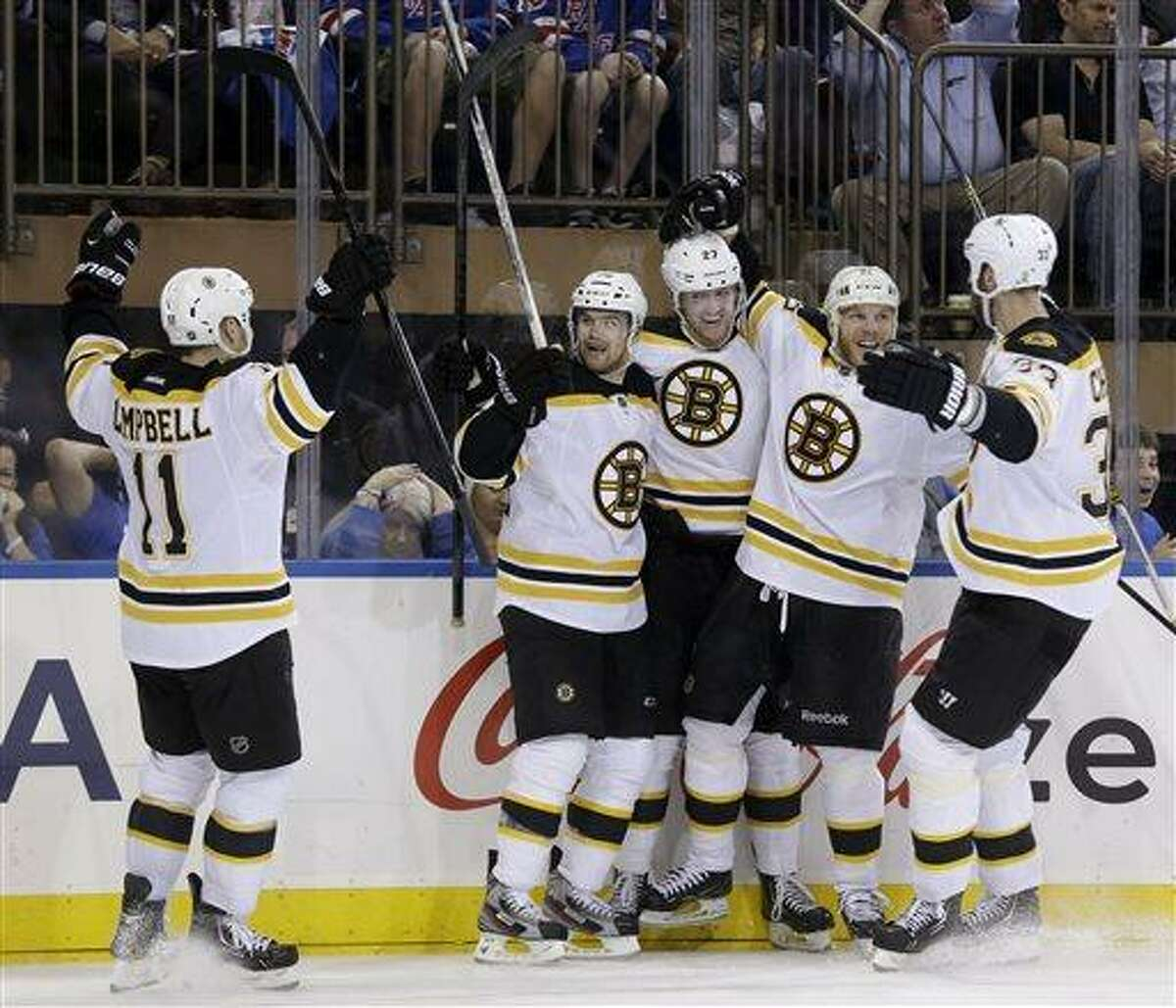 Boston Bruins' Daniel Paille, second from left, celebrates his game-winning goal with teammates Gregory Campbell, left, Dougie Hamilton, center, Shawn Thornton, second from right, and Zdeno Chara during the third period in Game 3 of the Eastern Conference semifinals against the New York Rangers in the NHL hockey Stanley Cup playoffs in New York Tuesday, May 21, 2013, in New York. The Bruins won 2-1 and lead the best-of-seven games series 3-0. (AP Photo/Seth Wenig)