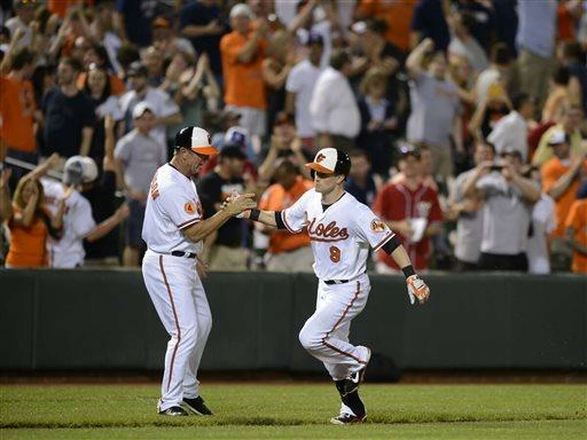 Baltimore Orioles third base coach Bobby Dickerson, left, greets Nate McLouth (9) after he hit the game-winning walk off home run against the New York Yankees in the 10th inning of a baseball game, Tuesday, May 21, 2013, in Baltimore. The Orioles won 3-2 in ten innings. (AP Photo/Nick Wass)
