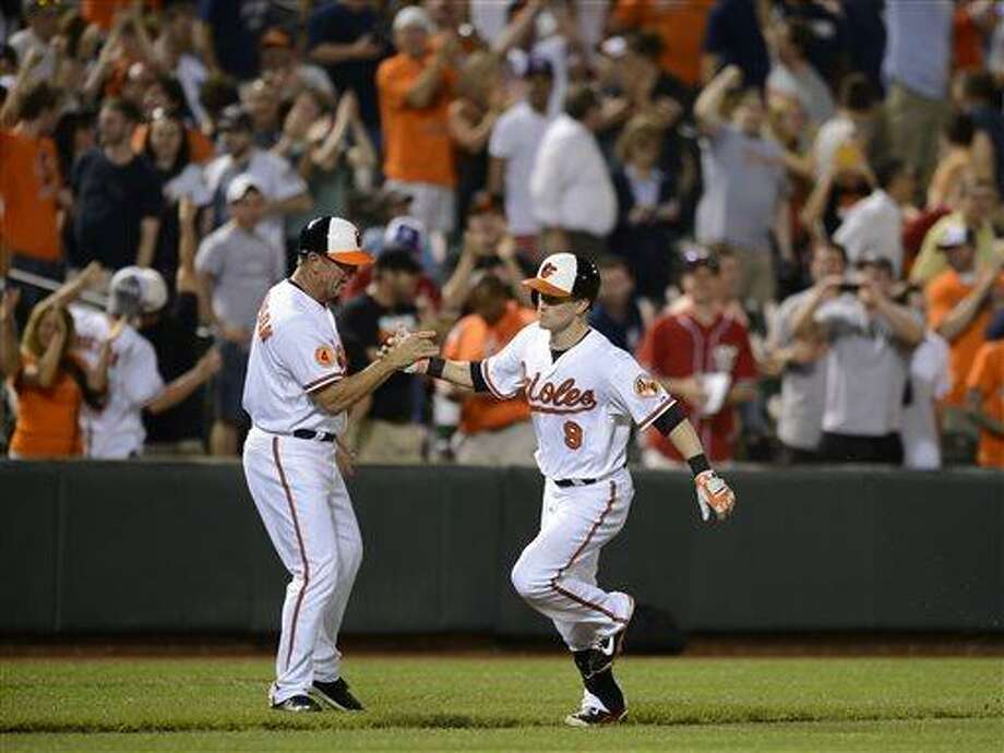 Baltimore Orioles third base coach Bobby Dickerson, left, greets Nate McLouth (9) after he hit the game-winning walk off home run against the New York Yankees in the 10th inning of a baseball game, Tuesday, May 21, 2013, in Baltimore. The Orioles won 3-2 in ten innings. (AP Photo/Nick Wass) Photo: ASSOCIATED PRESS / AP2013