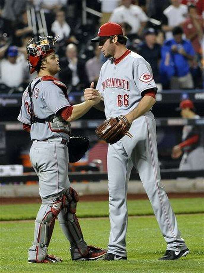 Cincinnati Reds catcher Devin Mesoraco congratulates Cincinnati Reds relief pitcher Logan Ondrusek (66) after the Reds shut out the New York Mets 4-0 in a baseball game at Citi Field on Tuesday, May 21, 2013 in New York. (AP Photo/Kathy Kmonicek) Photo: ASSOCIATED PRESS / AP2013