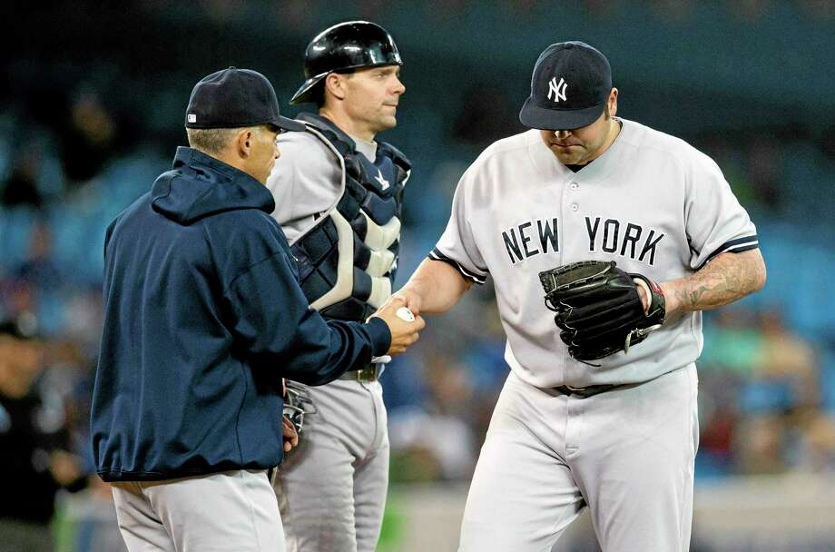Mark Blinch — The Canadian Press/The Associated Press The Yankees' Joba Chamberlain walks off the mound after being pulled by manger Joe Girardi, left, as catcher Chris Stewart, center, looks on against the Toronto Blue Jays Thursday. Photo: AP / The Canadian Press