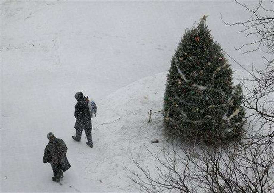 Snow falls as people walk by a Christmas tree at Military Park in downtown Newark, N.J., Wednesday, Dec. 26, 2012. The National Weather Service forecast sustained winds of 15 to 20 mph along the coast in the afternoon, with gusts up to 40 mph. The storm is expected to dump a total of four to six inches on the area and also produce sleet and freezing rain. Other areas are expected to get between two and three inches of rain. A flood watch has been issued from Wednesday afternoon through Thursday morning. (AP Photo/Julio Cortez) Photo: ASSOCIATED PRESS / AP2012