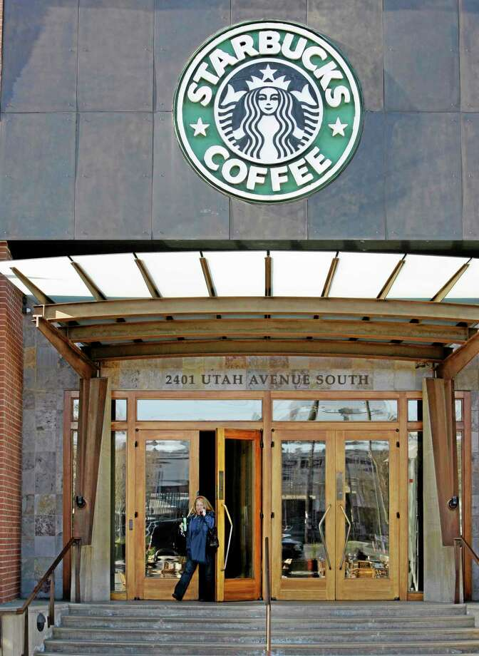 FILE - Starbucks' corporate headquarters is seen in this Monday, Jan. 26, 2009 file photo taken, in Seattle. Starbucks says guns are no longer welcome in its cafes, though it is stopping short of an outright ban on firearms. The Seattle-based company plans to buy ad space in major national newspapers including The New York Times, Wall Street Journal, Washington Post and USA Today on Thursday Sept. 19, 2013 to run an open letter from CEO Howard  Schultz explaining the decision.  (AP Photo/Elaine Thompson, File) Photo: AP / AP