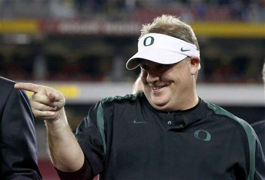 FILE - In this Jan. 3, 2013 file photo, Oregon head coach Chip Kelly celebrates with his players after the Fiesta Bowl NCAA college football game against Kansas State, in Glendale, Ariz. The Philadelphia Eagles have hired Kelly after he originally chose to stay at Oregon. Kelly becomes the 21st coach in team history and replaces Andy Reid, who was fired on Dec. 31 after a 4-12 season. (AP Photo/Ross D. Franklin, FIle) Photo: ASSOCIATED PRESS / A2013