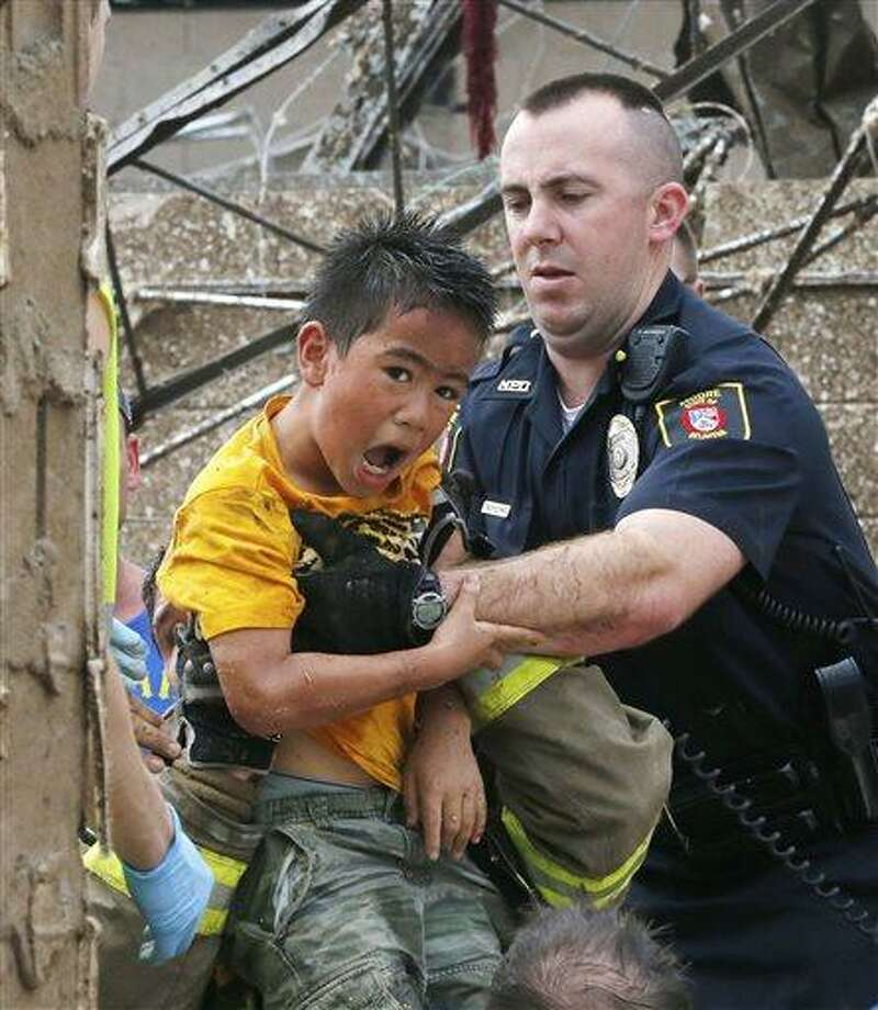 A boy is pulled from beneath a collapsed wall at the Plaza Towers Elementary School following a tornado in Moore, Okla., Monday, May 20, 2013. A tornado as much as a mile (1.6 kilometer) wide with winds up to 200 mph (320 kph) roared through the Oklahoma City suburbs Monday, flattening entire neighborhoods, setting buildings on fire and landing a direct blow on the elementary school. (AP Photo Sue Ogrocki) Photo: AP / AP