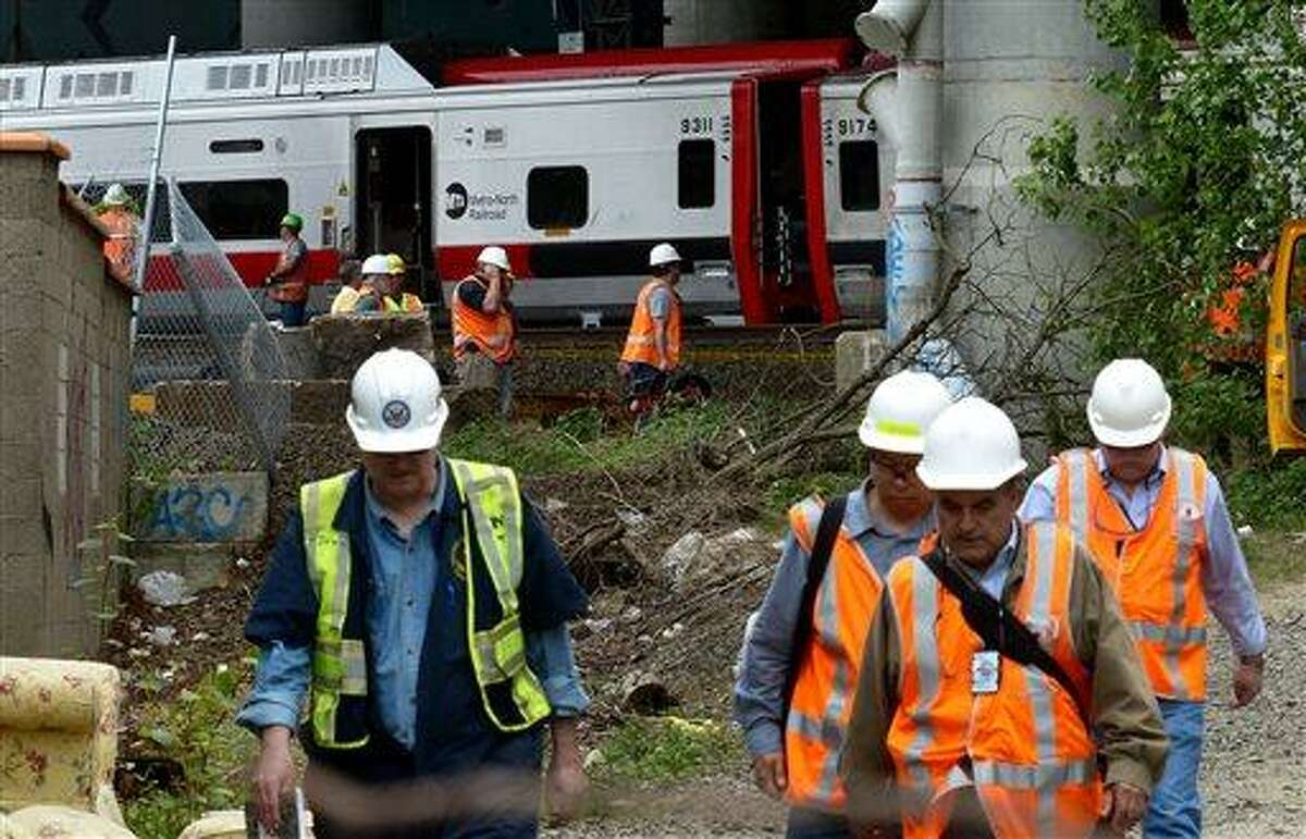 Metro-North Railroad officials tour the scene of the train derailment, Saturday, May 18, 2013 in Bridgeport, Conn. Officials described a devastating scene of shattered cars and other damage where two trains packed with rush-hour commuters collided in Connecticut, saying Saturday it's fortunate that no one was killed and that there weren't even more injuries. (AP Photo/Connecticut Post, Christian Abraham) MANDATORY CREDIT