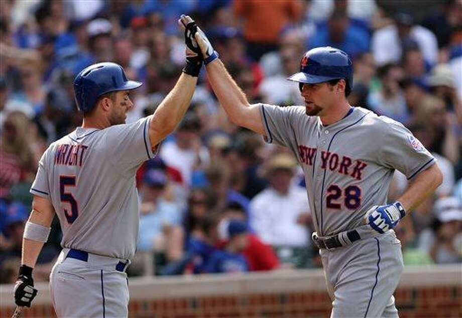 New York Mets' Daniel Murphy, right, is congratulated by teammate David Wright after hitting solo home run in the eighth inning of a baseball game against the Chicago Cubs in Chicago, Sunday, May 19, 2013. (AP Photo/Charles Cherney) Photo: AP / FR170067 AP