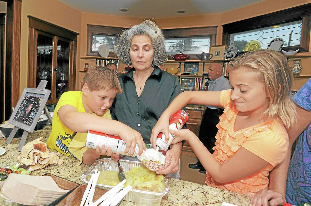 Matthew Dutka, left, with Charlene Dutka, owner of Ciesco Catering on South Main Street, and Jessica Manchak add whipped cream to a dessert during the third Torrington Dough presentation Thursday.