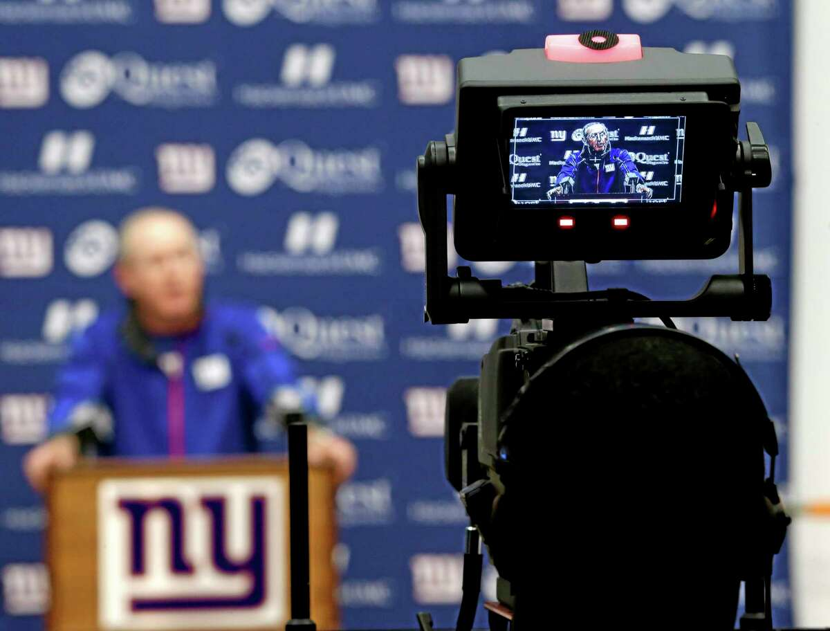 Giants head coach Tom Coughlin, displayed in the monitor of a video camera, talks to the media during an availability before the start of Wednesday's practice in East Rutherford, N.J. Coughlin's brother, John, died on Monday night.