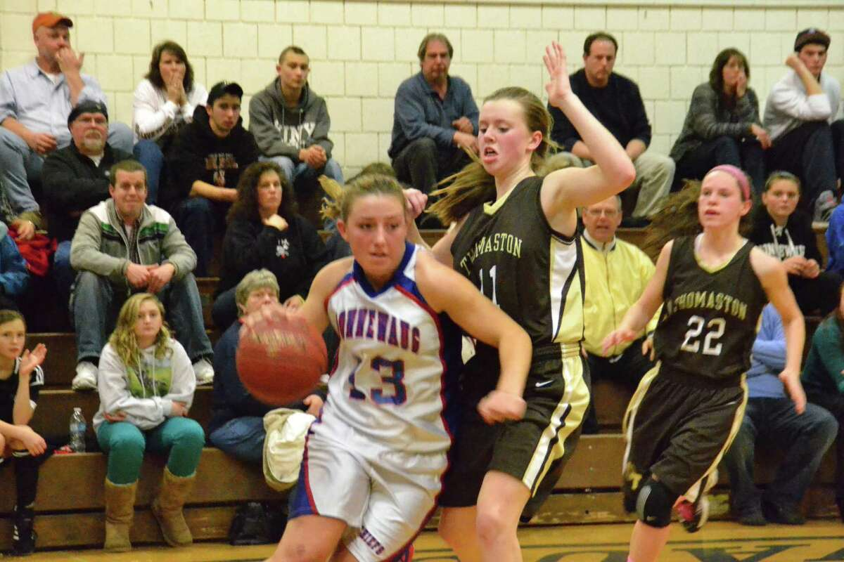 Nonnewaug's Katie Burke drives to the basket around a Thomaston defender in Tuesday's loss. Pete Paguaga/Register Citizen.
