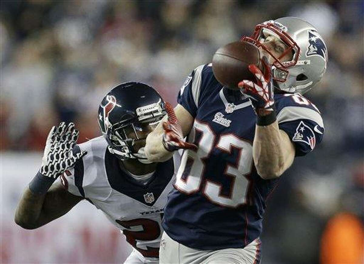New England Patriots wide receiver Wes Welker (83) pulls in a 47-yard pass from Tom Brady as Houston Texans cornerback Kareem Jackson chases him during the first half of an AFC divisional playoff NFL football game in Foxborough, Mass., Sunday, Jan. 13, 2013. (AP Photo/Elise Amendola)
